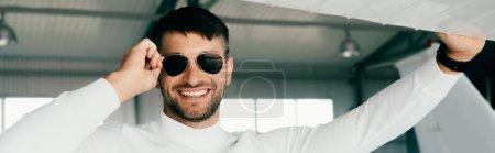 Photo pour Prise de vue panoramique de l'homme barbu souriant dans des lunettes de soleil regardant la caméra - image libre de droit