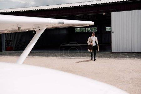 Photo pour Vue pleine longueur de l'homme dans le manteau avec le sac et l'avion au premier plan - image libre de droit
