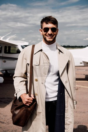 homme en manteau debout près de l'avion dans la journée ensoleillée