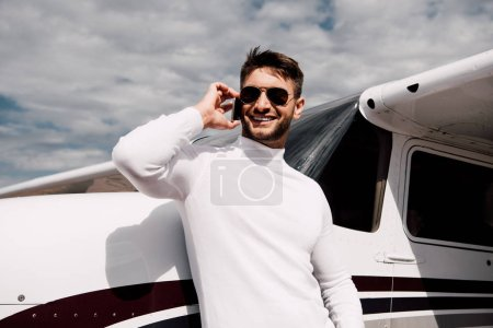 Photo for Smiling bearded man in sunglasses talking on smartphone near plane - Royalty Free Image