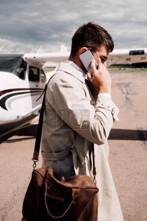 Photo pour Vue latérale de l'homme en manteau avec sac parlant sur smartphone près de l'avion - image libre de droit