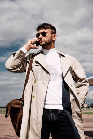 Photo for Low angle view of pensive man in coat with bag talking on smartphone near plane - Royalty Free Image