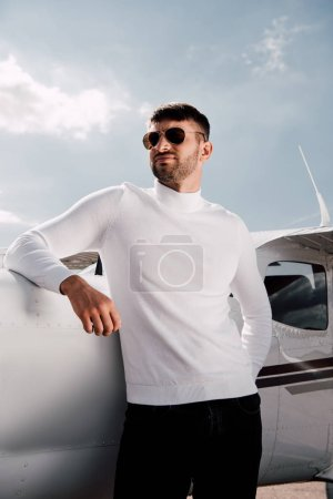 Photo for Low angle view of bearded man in sunglasses standing near plane in sunny day - Royalty Free Image