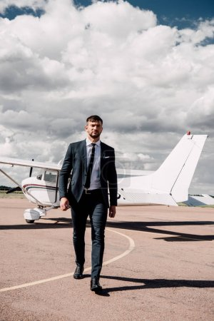 Photo for Full length view of businessman in formal wear walking near plane - Royalty Free Image