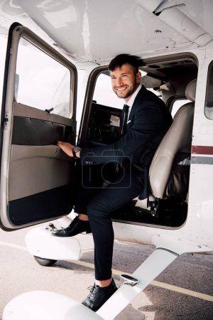 Photo for Smiling bearded businessman in formal wear sitting in plane - Royalty Free Image
