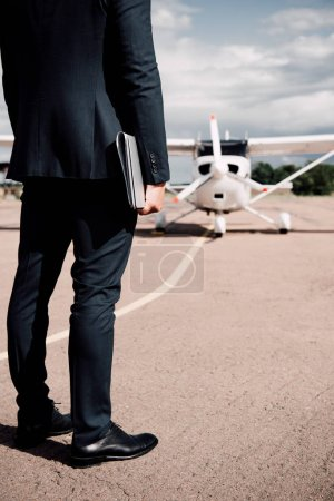 partial view of businessman in formal wear holding laptop and map in sunny day