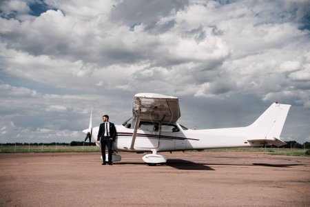 full length view of businessman in formal wear standing near plane in sunny day