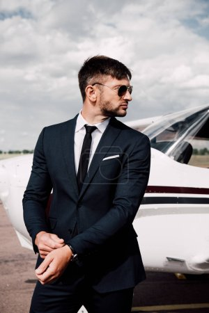 Photo for Pensive businessman in formal wear standing near plane in sunny day - Royalty Free Image