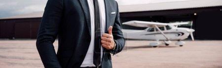 Photo pour Plan panoramique de l'homme d'affaires en tenue de cérémonie debout devant l'avion et montrant pouce vers le haut - image libre de droit