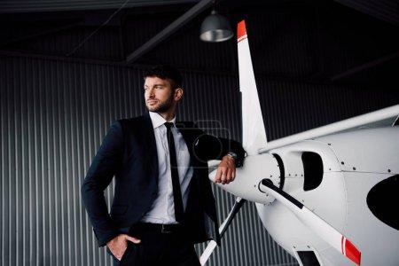 Photo pour Homme d'affaires confiant dans l'usure formelle restant avec la main dans la poche près de l'avion - image libre de droit