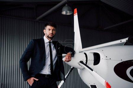 Photo pour Homme d'affaires confiant en tenue formelle debout avec la main dans la poche près de l'avion - image libre de droit