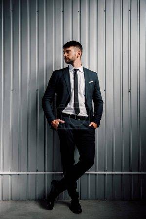 Photo pour Vue pleine longueur de l'homme d'affaires confiant dans l'usure formelle restant avec des mains dans des poches - image libre de droit