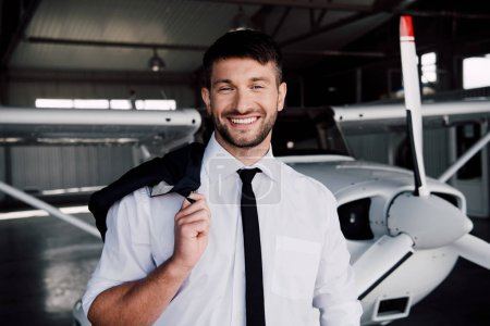 Photo for Smiling pilot in formal wear standing near plane and looking at camera - Royalty Free Image