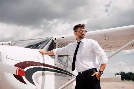Foto de Piloto confiado en gafas de sol de pie cerca del avión y mirando hacia otro lado - Imagen libre de derechos