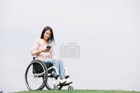Photo for Smiling disabled woman in wheelchair using smartphone while resting in park - Royalty Free Image