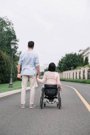 Photo pour Vue arrière de jeune homme retenant des mains avec la petite amie handicapée tout en marchant sur la route en stationnement - image libre de droit