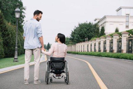 Photo pour Vue arrière du jeune homme et de la femme handicapée retenant des mains tout en marchant dans le stationnement - image libre de droit