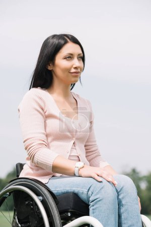 Photo for Happy disabled woman looking away while resting in park - Royalty Free Image