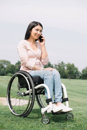 Photo for Happy disabled woman in wheelchair talking on smartphone while resting in park - Royalty Free Image
