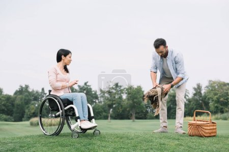 Foto de Hombre guapo que se prepara lugar para picnic cerca de novia discapacitada en el parque - Imagen libre de derechos