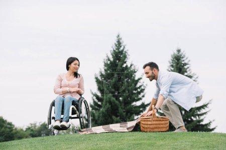 Foto de Hombre feliz preparando lugar para picnic cerca de novia discapacitada en el parque - Imagen libre de derechos