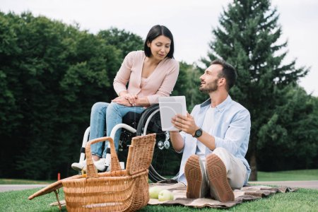 Photo for Cheerful disabled woman and smiling boyfriend using digital tablet in park - Royalty Free Image