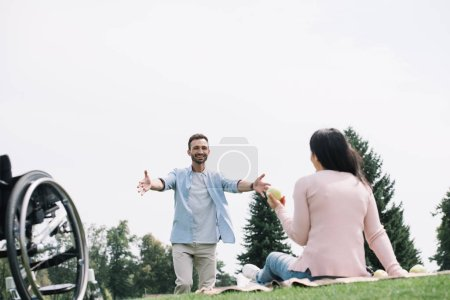 happy man gesturing near disabled girlfriend sitting on blanket and holding apple