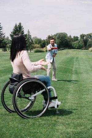 Foto de Joven alegre lanzando disco volador a la novia discapacitada en el parque - Imagen libre de derechos