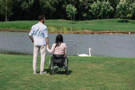 Photo pour Vue arrière de jeune homme retenant des mains avec la femme handicapée tout en regardant l'étang dans le stationnement - image libre de droit