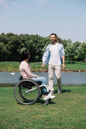 Photo pour Jeune homme gai avec la petite amie handicapée se reposant près du lac dans le stationnement - image libre de droit