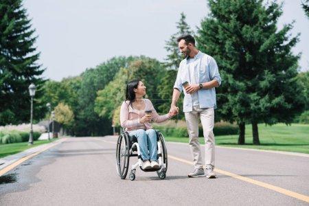 Photo pour Heureuse femme handicapée tenant la main avec beau petit ami tout en marchant dans le parc ensemble - image libre de droit