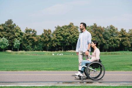 Photo pour Beau jeune homme retenant des mains avec la petite amie handicapée tout en marchant dans le stationnement ensemble - image libre de droit