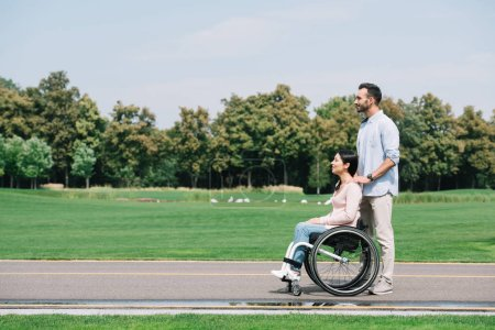 Photo for Happy young man walking in park with disabled girlfriend - Royalty Free Image