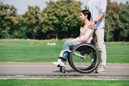 Photo for Cropped view of young man walking in park with disabled girlfriend - Royalty Free Image