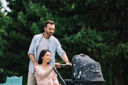 Photo pour Femme handicapée heureuse et mari marchant avec le chariot de chéri dans le stationnement ensemble - image libre de droit
