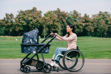 Photo for Young disabled woman in wheelchair walking with baby carriage in park - Royalty Free Image