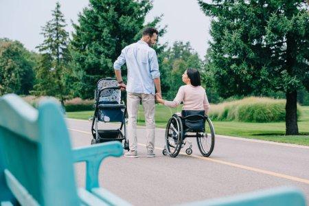 Photo pour Foyer sélectif de femme handicapéheureuse retenant des mains avec le mari tout en marchant avec le chariot de chéri dans le stationnement ensemble - image libre de droit