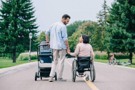 Photo pour Main heureuse de fixation d'homme de la femme handicapée tout en marchant avec le chariot de chéri dans le stationnement ensemble - image libre de droit