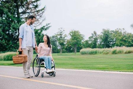 Photo pour Bel homme avec le panier de paille retenant des mains avec la petite amie handicapée tout en marchant dans le stationnement ensemble - image libre de droit