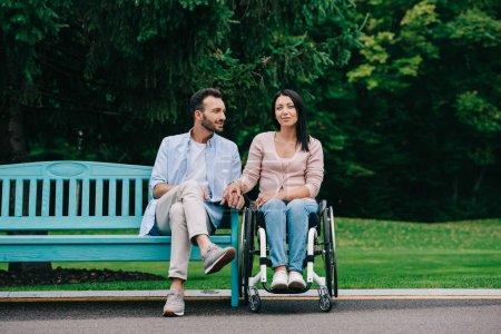 Photo pour Bel homme avec la femme handicapée heureuse se reposant dans le stationnement ensemble - image libre de droit