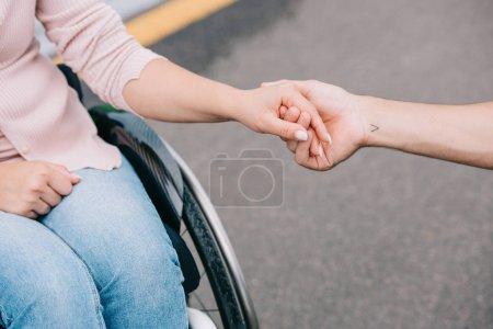 Photo pour Vue partielle de la femme handicapée retenant des mains avec le petit ami - image libre de droit