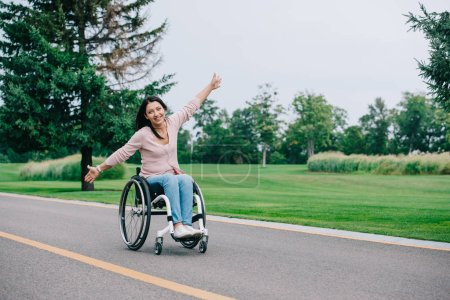 Photo for Happy disabled woman gesturing and looking at camera while sitting in wheelchair in park - Royalty Free Image