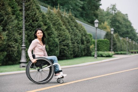 Photo for Beautiful disabled woman in wheelchair smiling at camera while walking in park - Royalty Free Image
