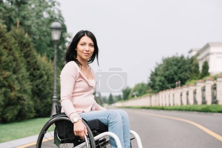 Photo for Young disabled woman in wheelchair smiling and looking at camera - Royalty Free Image