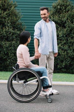Photo pour Homme heureux retenant des mains avec la petite amie handicapée tout en marchant dans le stationnement ensemble - image libre de droit