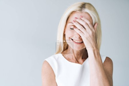 Photo for Happy blonde mature woman with closed eyes isolated on grey - Royalty Free Image
