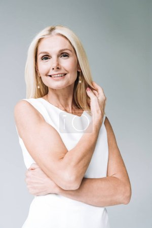 Photo for Happy blonde mature woman looking at camera isolated on grey - Royalty Free Image