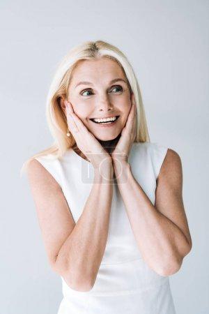 Photo pour Femme mûre blonde de sourire regardant loin d'isolement sur le gris - image libre de droit