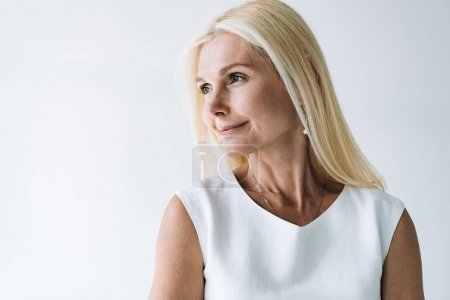 Photo for Smiling blonde elegant mature woman looking away isolated on grey - Royalty Free Image