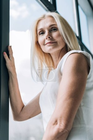 Photo for Low angle view of elegant blonde mature woman looking at camera near window - Royalty Free Image